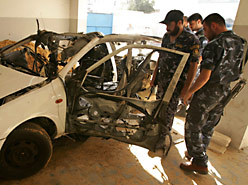 Hamas militants inspecting the car in which senior Islamic Jihad member Raed Fanuna was killed east of Gaza City on Tuesday. (AP Photo)