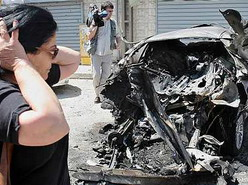 A woman inspecting the damage done to a car in Sderot on Tuesday, following a week-long barrage of Qassam rockets. (Roni Shizer/Jini)